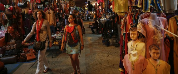 "Tourists stroll between shops in Rue des Consuls in Rabat's Medina September 25, 2014. UNESCO made Rabat a World Heritage Site two years ago and media and tour operators call it a ""must-see destination."" But it seems the tourist hordes have yet to find out. While visitors are getting squeezed through the better-known sites of Marrakesh and Fez, the old part of Rabat - with its beautiful Medina and Kasbah of the Udayas - remains an almost unspoiled oasis of calm. Smaller and more compact, its labyrinths of streets, passages and dead ends are a treasure trove of shapes and colours, of moments begging to be caught by the photographer's lens. Picture taken September 25, 2014.    REUTERS/Damir Sagolj (MOROCCO - Tags: BUSINESS SOCIETY TRAVEL)"